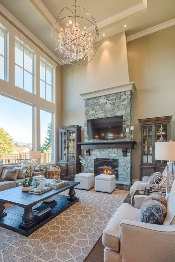 Large living room with two story windows, gorgeous lighting, large area  rug, stone