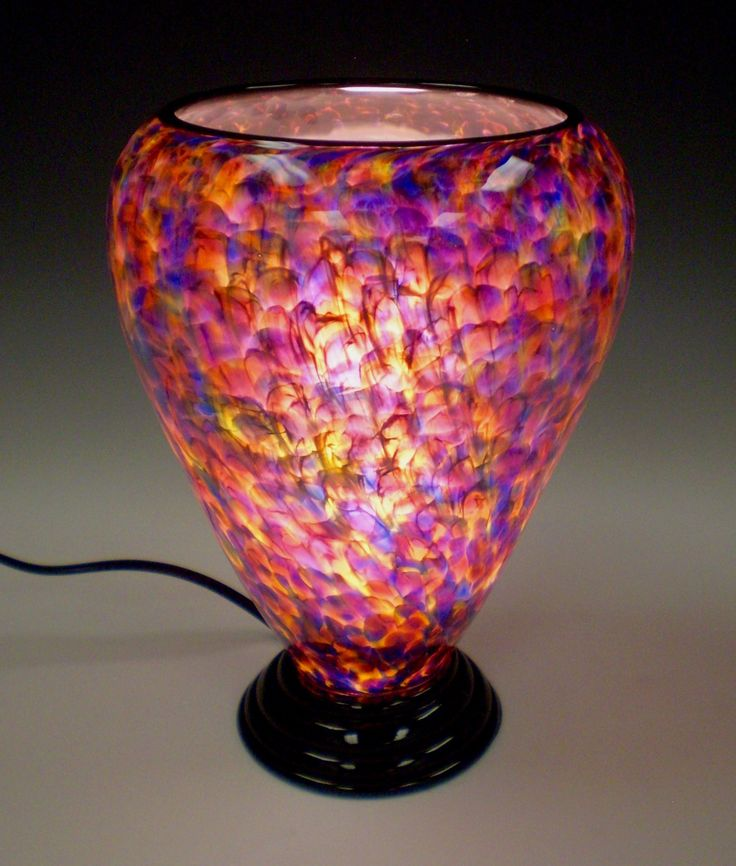 Speckled Crimson Lamp by Curt Brock. This is a hand blown glass lamp that has black trim on top and black foot. When lit, it has a warm luminescent quality. During the day, it is a beautiful object on its own, and it comes to life at night. Each piece is unique. Dimensions and pattern will vary slightly. Takes one 90-watt (maximum) incandescent or compact fluorescent bulb (not included).