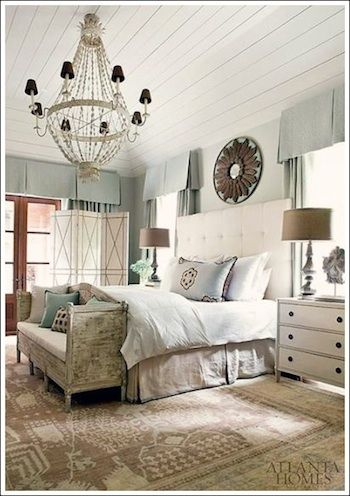 This romantic bedroom decor includes a chandelier, large white tufted headboard, antique white dresser and distressed bedroom bench. The cream, blue and beige color scheme ties everything together.