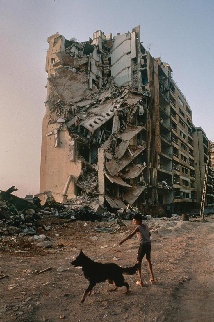 Photojournalism  Boy walking his dog near a destroyed building | Lebanon. This photo shows how a boy is walking his dog near a very badly destroyed building which was probably cause by a bomb. i feel as it shows that everyday life can be destroyed somehow but you can always ignore it and walk around as shown the boy doesn't really care about the building and is still going on with his life.