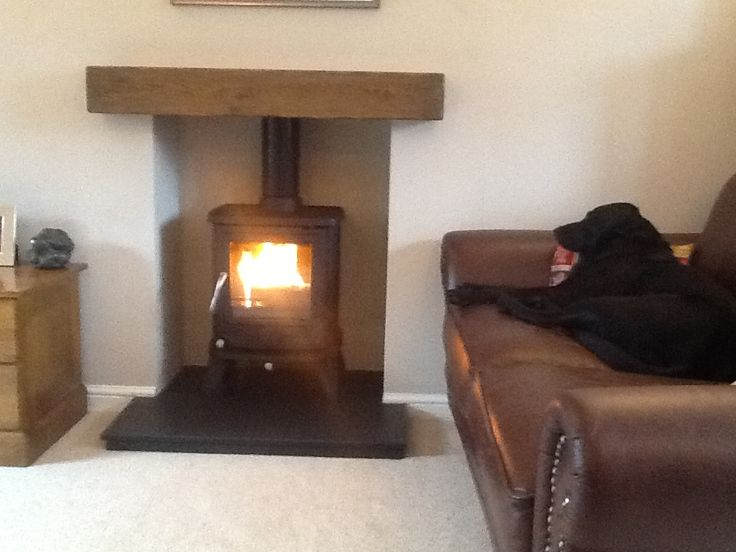 Wood burning stove with vintage distressed oak railway sleeper mantle.  Sleeping black Labrador, open fire, brown leather chesterfield sofa.
