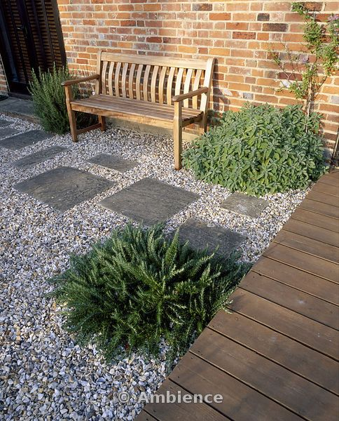 Ambience Images | Gravel garden beside the house with wooden bench, wooden decking and Stepping Stones. Designer - Mark Laurence