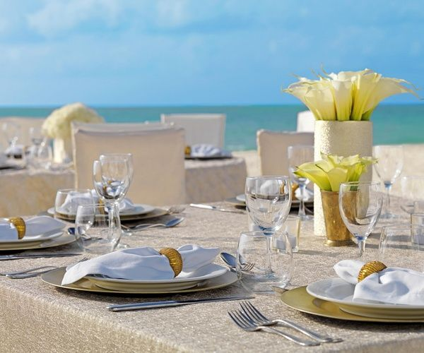 Neutral glam table setting with linen, gold and white lilies | Pearl Shimmer Collection at Palace Resorts #destinationwedding