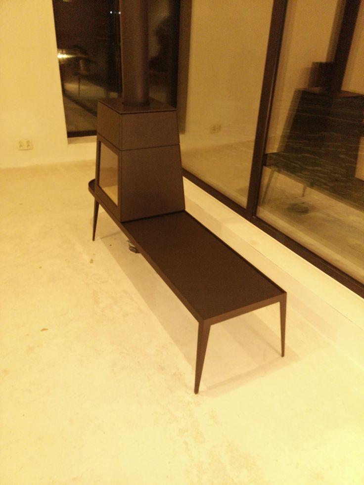 Designerski kominek Shaker firmy Skantherm, tym razem w opcji z dłuższą ławeczką. Projektant Antonio Citterio & Toan Nguyen.