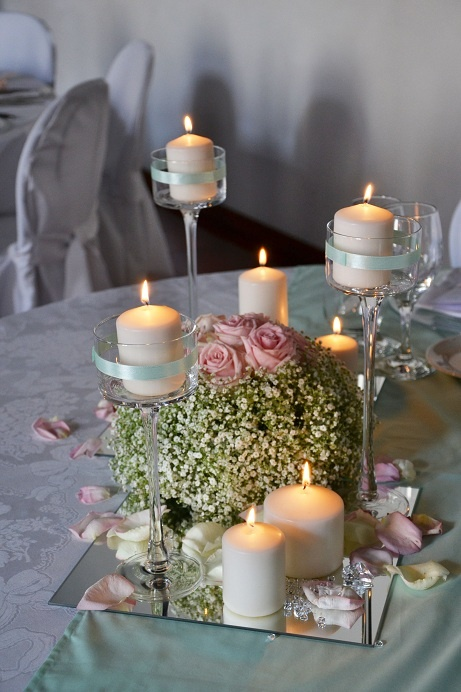 Romantic reception dinner centrepiece with white candles and baby's breath on a mirror base.