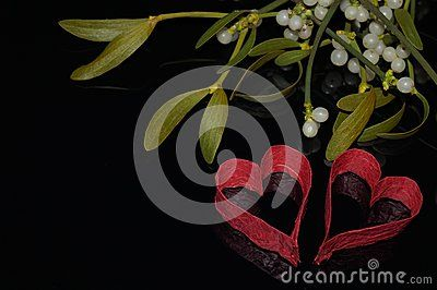 Red hearts and mistletoe on black background
