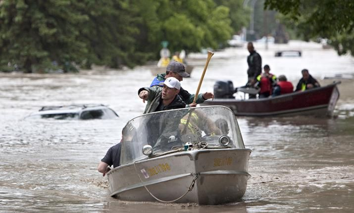 Rescuers looks for stranded residents in High River, Alta. on June 20, 2013 after the Highwood River overflowed its banks. THE CANADIAN PRESS/Jordan Verlage