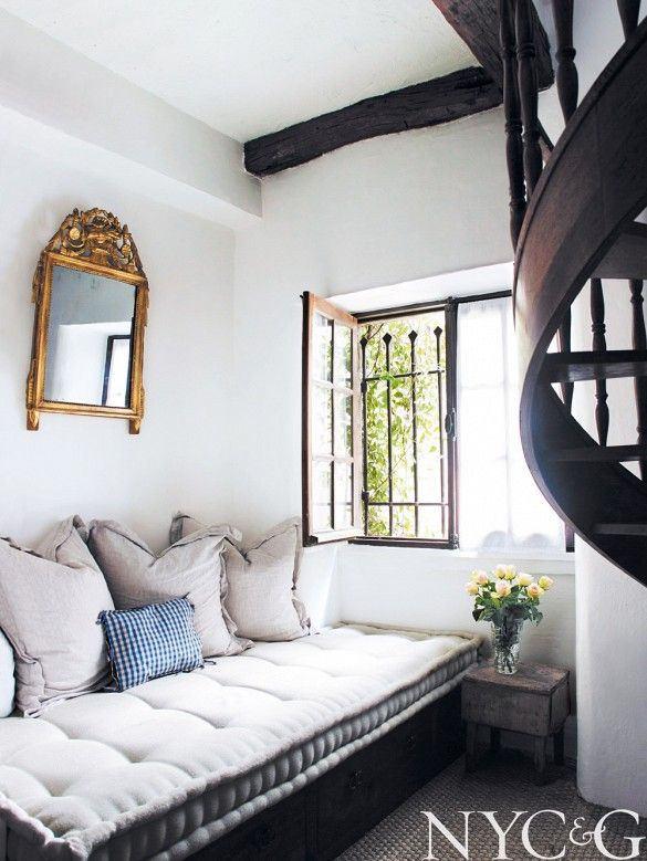 Linen tufted daybed with golden accent mirror and wood spiral staircase