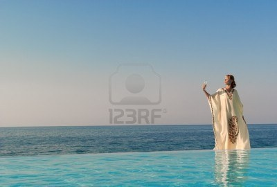 Greek style woman with glass of wine stand on the edge of infinity pool near seaside Stock Photo