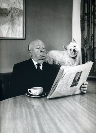 Alfred Hitchcock and his terrier reading the newspaper.