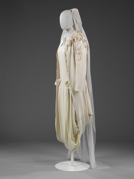 Roses of ivory silk cluster and trail over the shoulder and back of this wedding outfit.l Victoria and Albert Museum