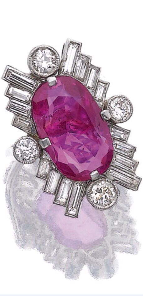 Ruby and diamond ring, late 1930s. The oval ruby claw-set within a surround of baguette and circular-cut diamonds, via Sotheby's