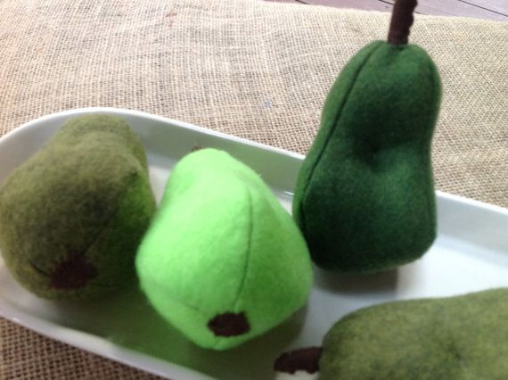 Felt pear for pretend play and great in any kitchen decor centerpiece.This felt pear is the size of a real pear. The green felt varies but each pear has a brown stem, a brown felt bottom and is dimpled to give the shape of a real pear. This pear encourages creative play as well as encouraging nutritious eating. This pear goes nicely with the other fruits in Marmies Market collection of felt fruit and veggies. This pear also blends with other fall food decor for your grown-up kitchen too…