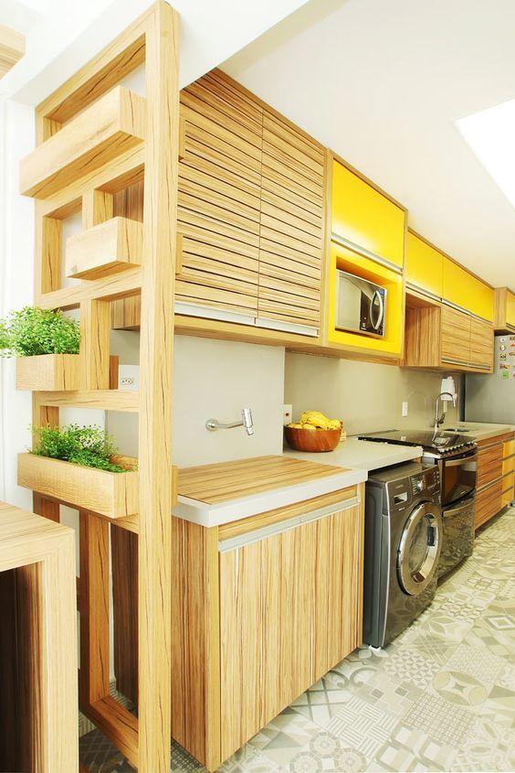 Cozinha em amarela e tons madeirados; Máquina de lavar integrada ao ...
