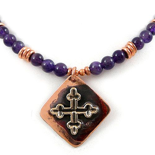 """Amethyst Necklace with Copper Mission Cross Pendant. Enhanced with copper beads, the amethyst necklace provides the foundation for a Mission Cross pendant handcrafted of polished reclaimed copper. A popular heraldry symbol for glory, faith, protection, and spirit, the Mission Cross is a crosslet composed of 4 Latin crosses, each facing the 4 cardinal directions.  The necklace measures 18"""" in length."""