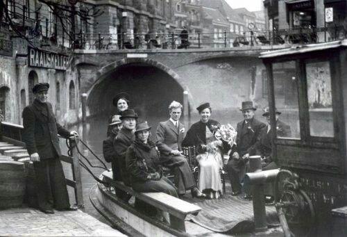 Een bruidspaar in Utrecht komt tijdens de Tweede Wereldoorlog per sleepboot naar het stadhuis aan de gracht, Nederland, 1940.