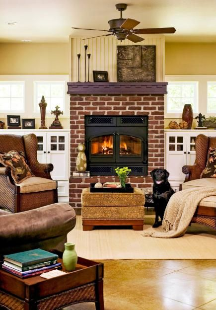 Relaxed feel - Comfy chairs, an upholstered ottoman and a brick fireplace all suggest a relaxing place to read or chat. The warm palette of brown, brick red and gold enhances the coziness of the room.