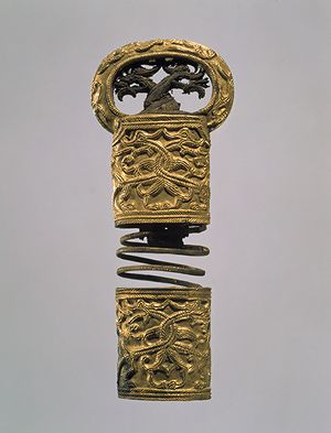 Gold Hilt with Oval Pommel, Three Kingdoms period, Silla Kingdom (57 B.C.–668 A.D.), 5th–6th century  Korea  Gold; L. 5 3/8 in. (13.8 cm), Diam. of pommel 2 1/4 in. (5.8 cm)  Treasure no. 776  Leeum, Samsung Museum of Art      Two intertwined dragons, set in relief, decorate the body of this gold hilt. Similarly, the heads of two dragons–with jade for eyes–fill the opening of the oval pommel. This motif reflects Central Asian and Siberian influences on Silla art...
