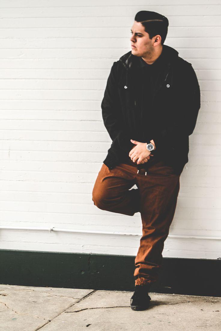 Shop this look on Lookastic:  https://lookastic.com/men/looks/bomber-jacket-polo-sweatpants-low-top-sneakers-watch/7206  — Black Wool Bomber Jacket  — Black Leather Watch  — Brown Sweatpants  — Black Suede Low Top Sneakers  — Black Polo
