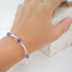 purple wire wrapped bangle bracelet - photo only - suggest wire wrap 3 wires together, add bead to center wire, wire wrap and repeat to proper bangle length. Have not decided on end. Maybe wire wrap the 6 ends in a wide wrap or connect with a dangle. Let me know how you finish this neat bangle.