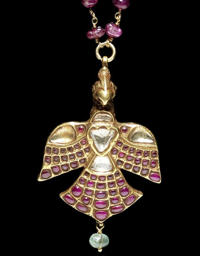 A gem-set gold Pendant in the form of a Bird  Deccan, 18th Century set with diamonds and rubies, depicted with open wings, head and back engraved with naturalistic feather details, emerald bead suspended from the tail, suspension loop attached to small tuft on head, on a twisted gold wire chain with ruby beads