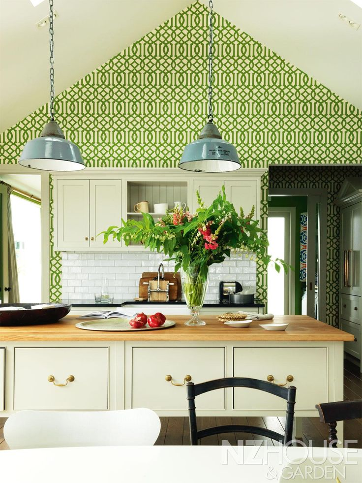 Green imperial trellis wallpaper lines the walls in this christchurch home with an oak kitchen joinery and antique