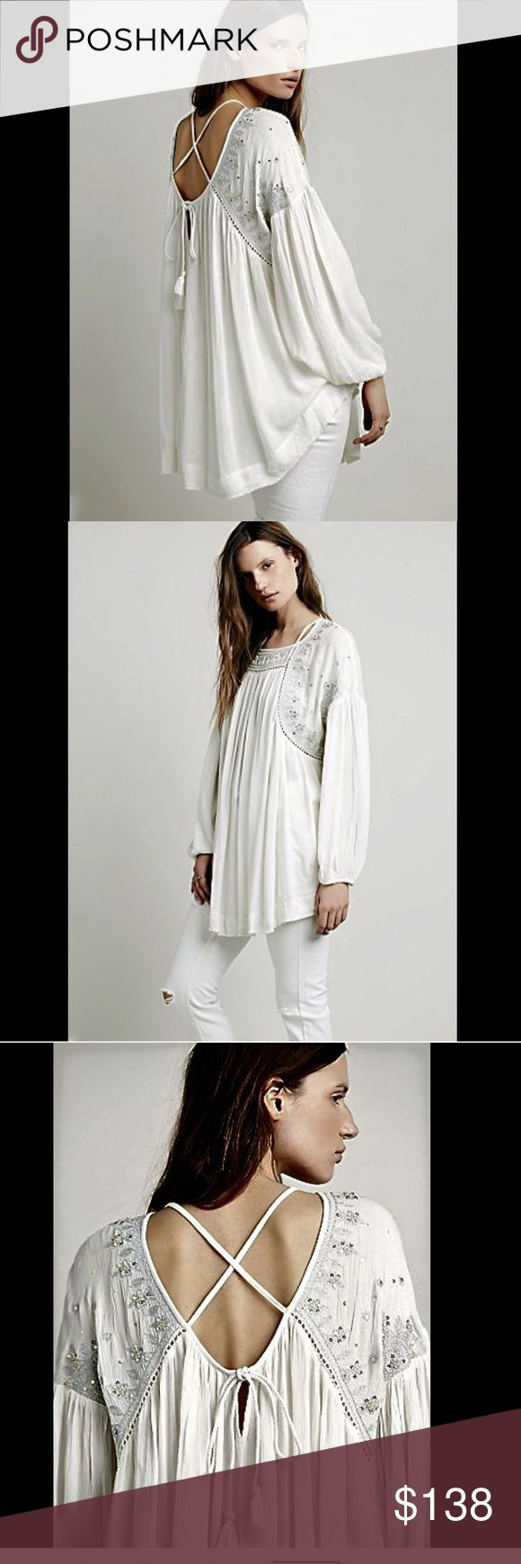 """Free People ivory white Swingy Embellished  Top S Free People ivory white Swingy Embellished Strappy Back Tunic Top Oversized & shapeless drapy flowy rayon crinkled crepe Silver metallic embroider, beadwork & sequins on the yoke & shoulders Features eyelet trim, a slinky strappy back with tassel ties, gathered cuffs full swing body longer in middle with raw hem New Without Tags  *  Size:  Small  * there is a dot on the tag to prevent store return  measures: 52"""" around bust 30"""" long in middle…"""