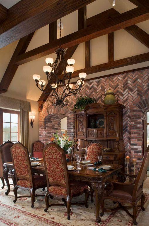 Обеденная комната в готическом стиле: потолок с деревянными балками, декоративный кирпич на стенах, большие окна и стилизованная мебель