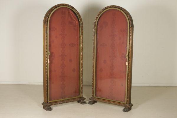 Ante con cornice in ferro e vetro antico. Struttura lignea del XX secolo intagliata e retta da piedi ferini.