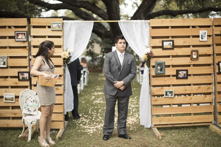 """Bride and groom took pallets and upcycled them into a """"wedding wall."""" This delineated the ceremony space for their outdoor wedding and served as a photo wall where they hung pics of themselves throughout their relationship as well as photos to honor relatives from both sides who were deceased. Bride says it warmed her heart to have them be a part of the ceremony :)"""