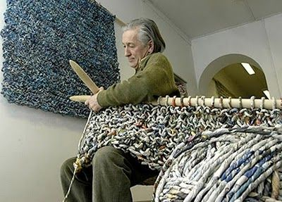 he uses newspapers to make long length of paper yarn, which rolls up in to large balls and then he crochets, knits or weaves with huge equipment  - look at the huge knitting needles he is using.  Go visit this site to see more of his art and then follow the link to his web site