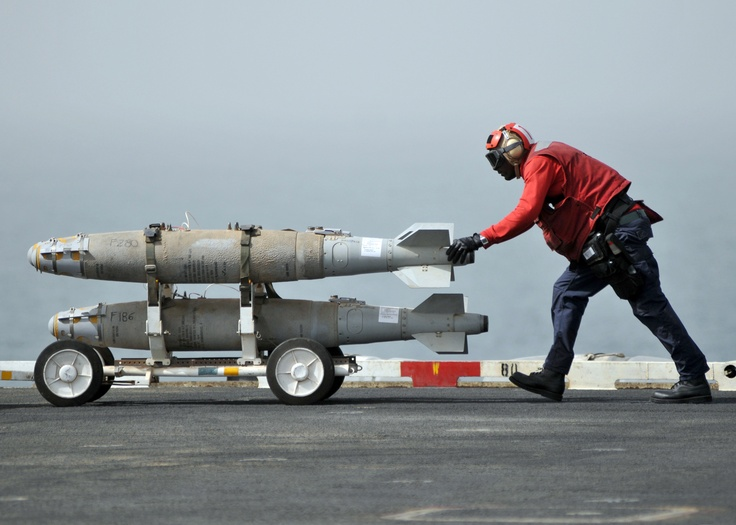 Aviation Ordnanceman moving Mk-82 munitions on the USS Abraham Lincoin.