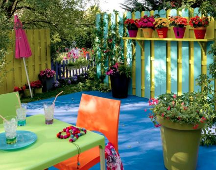 décoration de balcon mobilier de jardin vert et orange sur tapis de sol extérieur bleu vif, palissade bois et jarres de couleurs vives