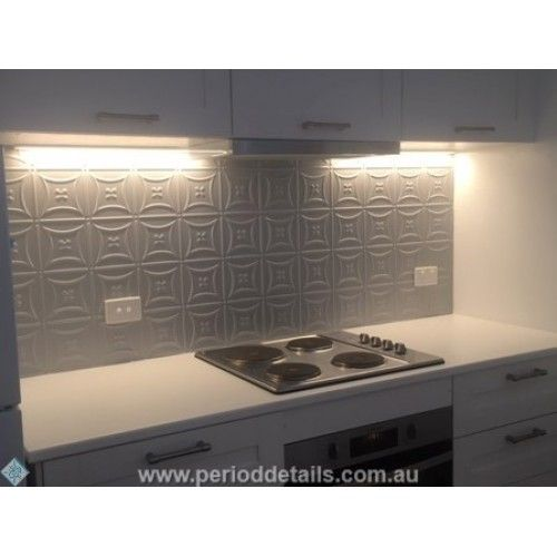 The Carnivale Pressed Tin Panel powdercoated in Dulux Duralloy Anotec Silver Grey works fantastically as a splashback in this small apartment kitchen.