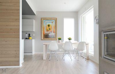 The Scandinavian dining room with colorful art, wood and grey fireplace. Interior design by Marika Ritala-Mäkinen (Finland, Tampere). Painting by Terry Laakso.  #scandinavian #diningroom #dining #painting #flowers #grey #walls #vinylcork #floor #designtalo #topikeittiot #siparila #woodpanel