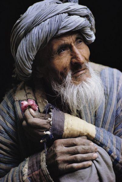 Mahmad Niyaz, Mai 1967. 'L'Afghan à la rose, sellier dans le bazar de Tashkourgan interrompt de temps en temps son travail pour respirer une rose avec une infinie délicatesse. Le vieil artisan semble alors s'évader de ce monde.' Photo et légende deRoland et Sabrina Michaud