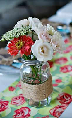 The way the flowers are arranged--and the types they chose--make this twine-wrapped mason jar centerpiece look elegant!