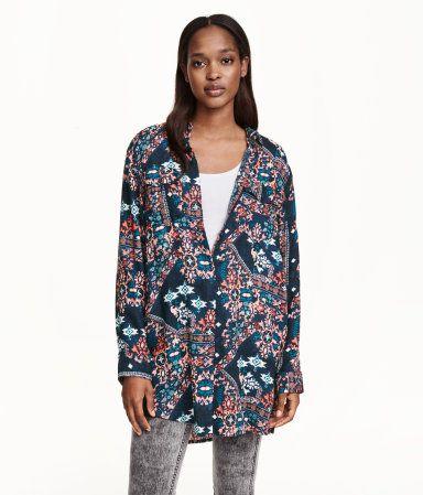 Een lange, gedessineerde overhemdblouse van geweven kwaliteit met lange mouwen en borstzakken met klep en knoop.