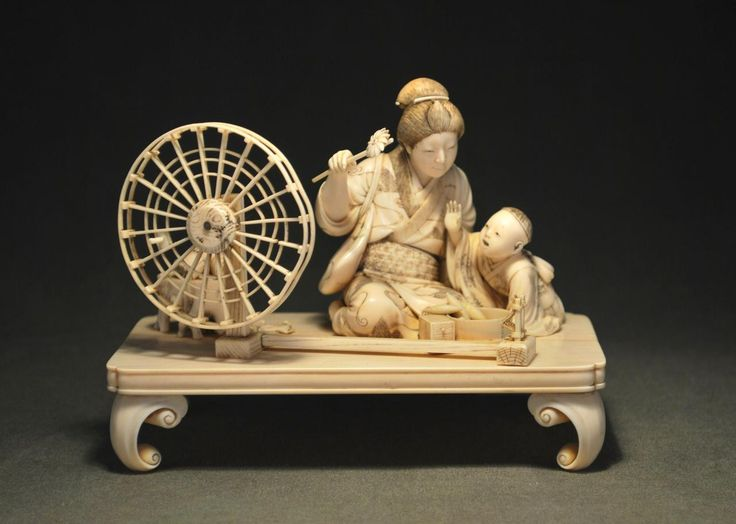 Japan. An ivory okimon, mother and son with spinning wheel. Artist: signed Shizumasa Ookawa. Date: late 19th Century (Meiji Period). Size: height 11.4 cm, width 14.6 cm