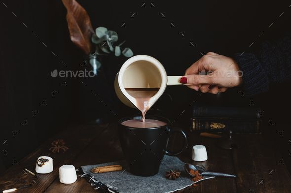 Female Pouring Hot Chocolate Drink from Milk Pan into Black Mug on Rustic Table - Stock Photo - Images Download here : https://photodune.net/item/female-pouring-hot-chocolate-drink-from-milk-pan-into-black-mug-on-rustic-table/18917530?s_rank=5&ref=Al-fatih