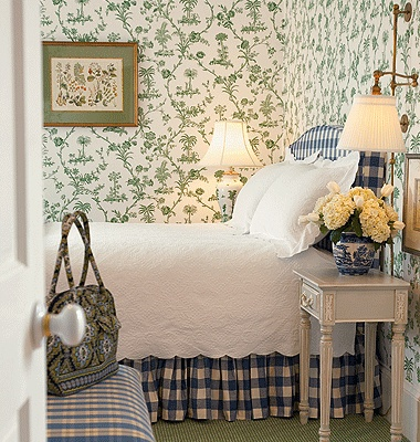 I love the floral wallpaper in green and white, especially together with the classic blue and white textiles. A country chic bedroom.