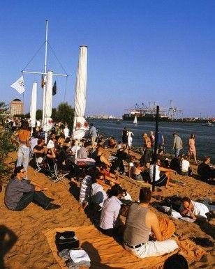 Strandperle, Hamburg Othmarschen Mit dem Füßen im Sand einen Sundowner an der Elbe genießen.