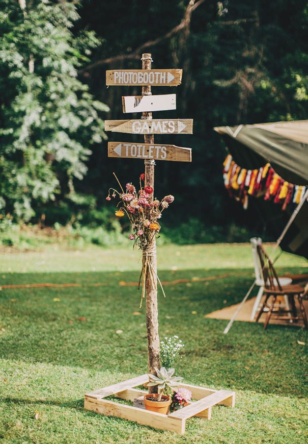 Standing wooden wedding directions sign with flowers tied to the post.