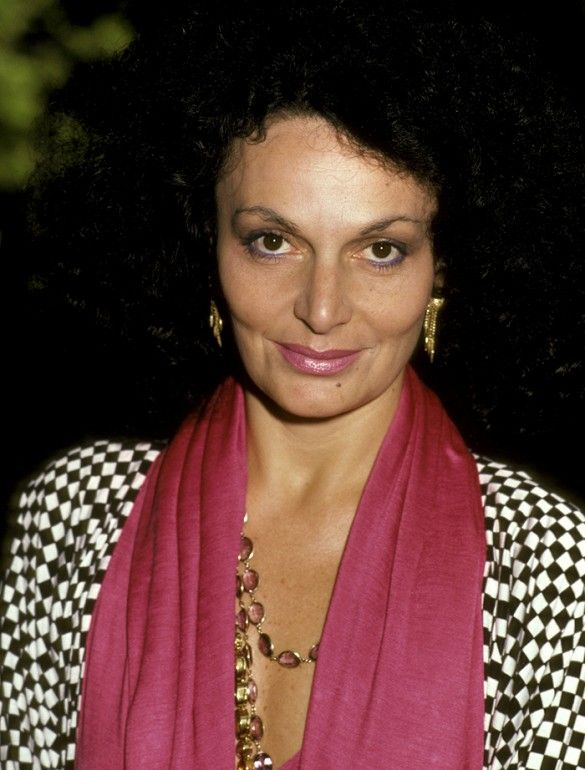 Diane von Furstenberg in a checkered blouse accessorized with a pink scarf.