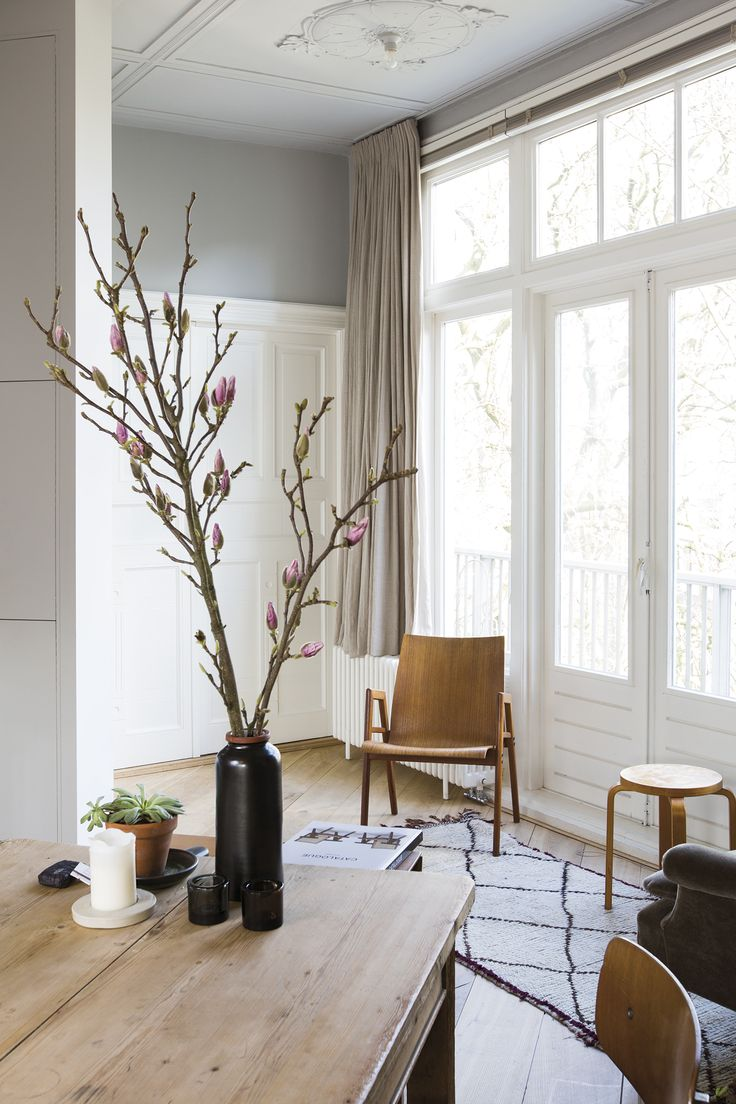 Dining area with wooden chair and stool 60 by Artek and a branch of magnolia in the home of interior architect Stef Bakker | Coffeeklatch