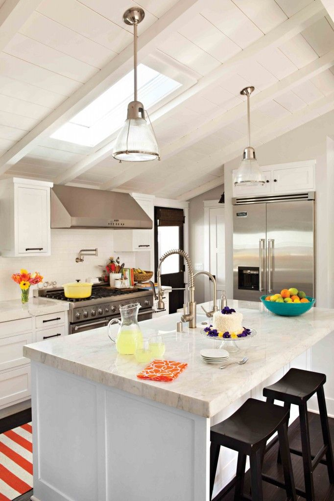 Adorable cottage kitchen. Just enough colour to make it charming. The vaulted ceilings and all white envelope are darling.