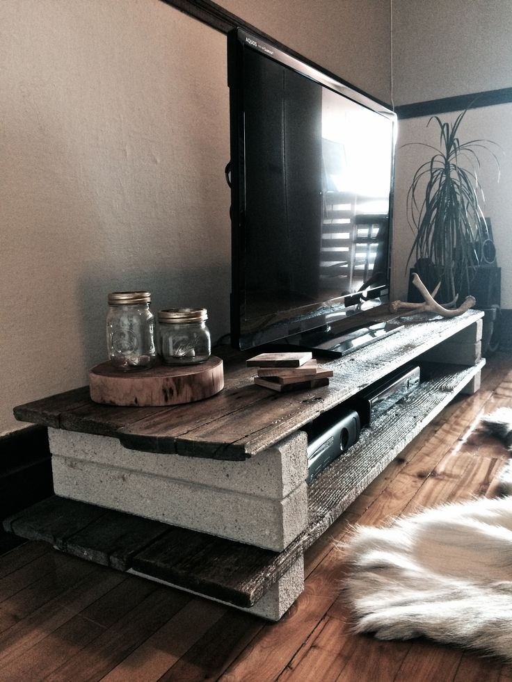 DIY - Barn wood media stand Take a few planks, apply satin varnish on it and separate them with white bricks. Don't even need a hammer!