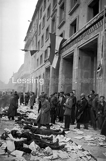 Dead members of the Secret Police, ordered to protect the Budapest headquarters of the Communist Party, lie lined up in front of the just conquered building.