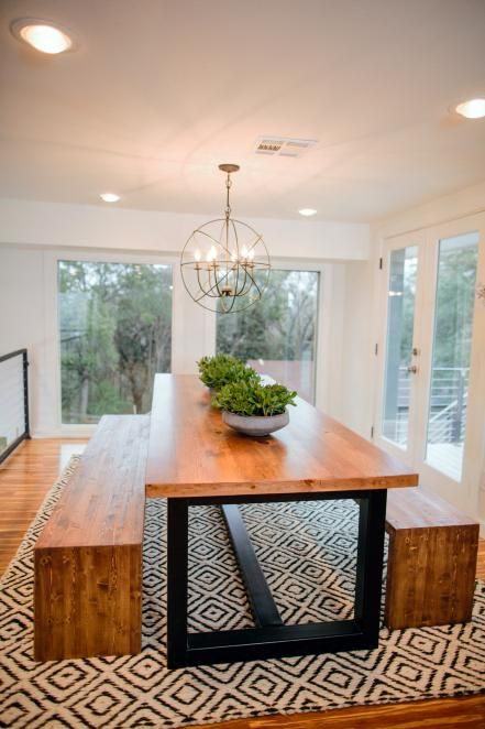 Modern, sleek, minimalist dining room. Geometric sphere metal wire gold chandelier. Large wood and steel dining room table. Brown wood benches for dining chairs. Plants on top of table to accent. White room walls.