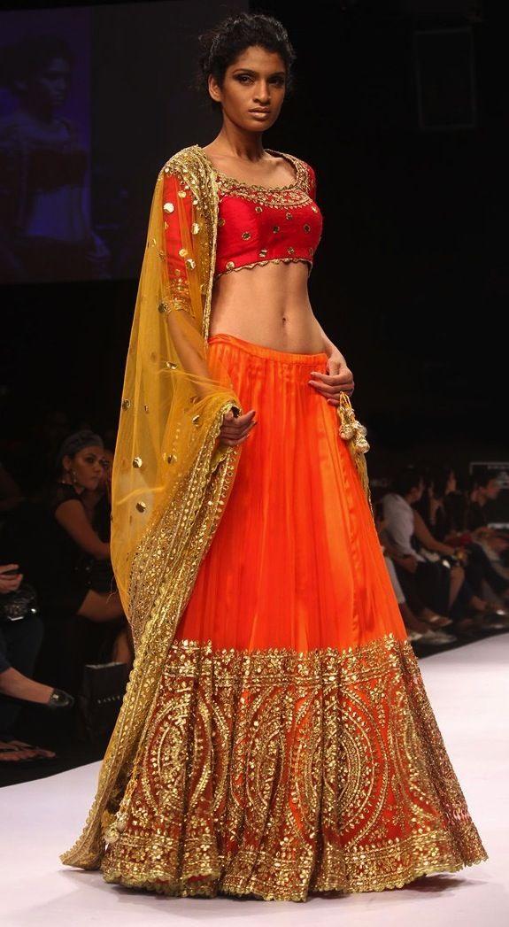 Orange net lehanga, red blouse, yellow dhupatta with heavy gota work